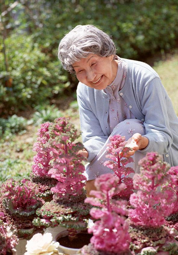 庭で花の咲き具合を見ている年配女性
